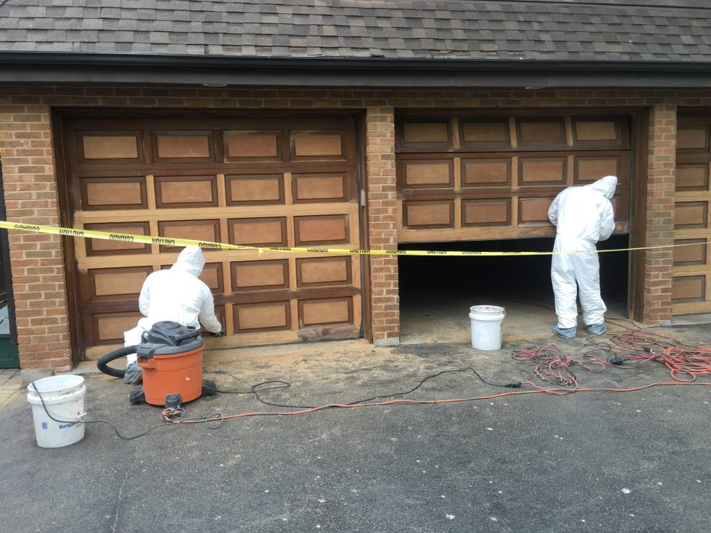 men renovating garage doors