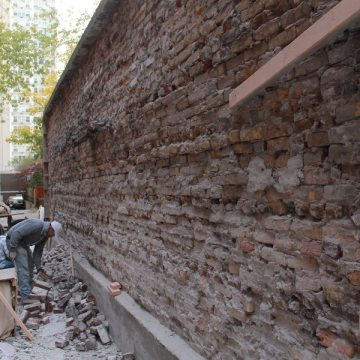 Man observing damaged brick wall