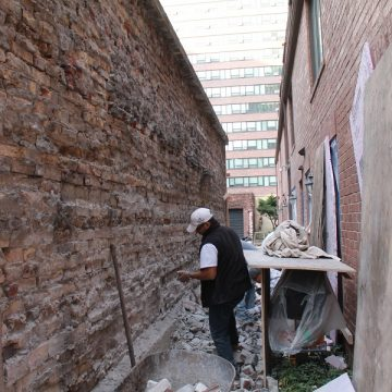 man working on damaged brick wall