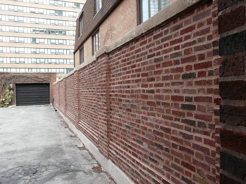 Brick wall leading to a garage door
