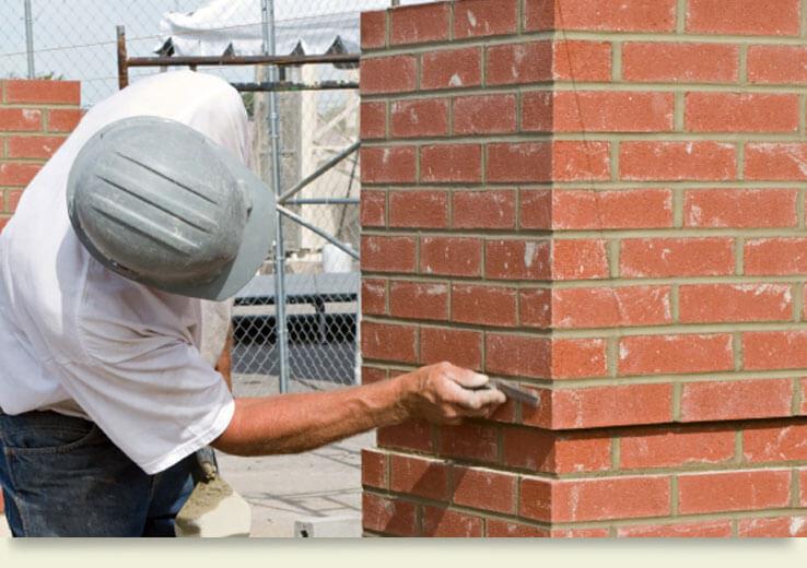 Man adding mortar to bricks