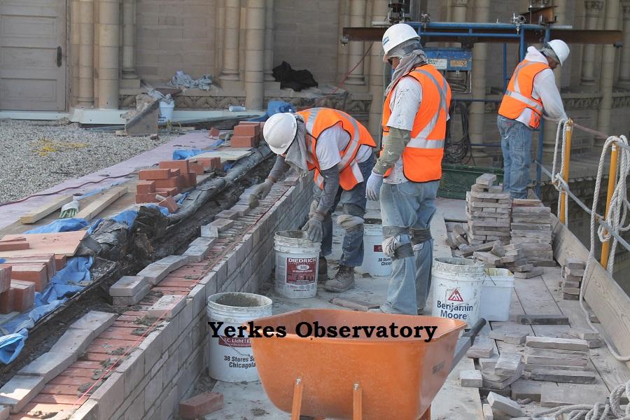 men performing brick work on roof