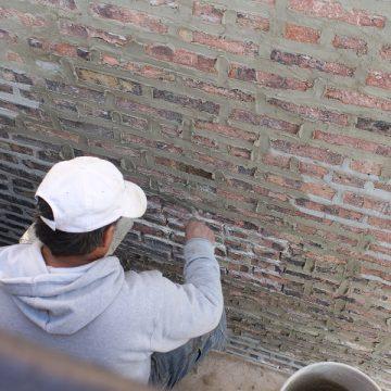 Man finishing brick wall morter