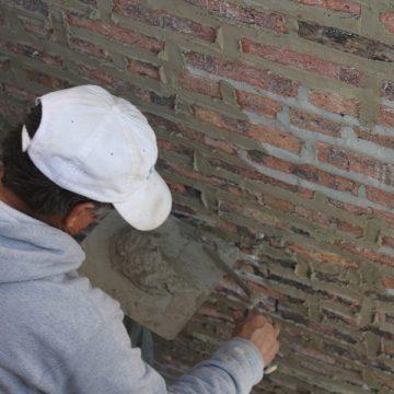 man applying plaster to brick wall
