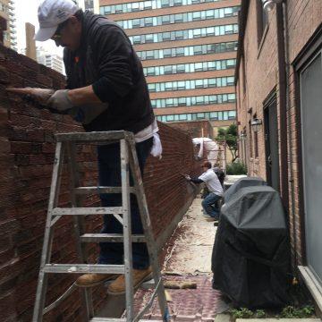 Man on ladder working on brick wall