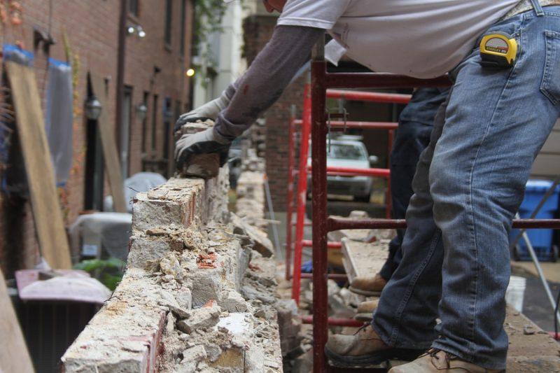 Man placing brick on wall under construction