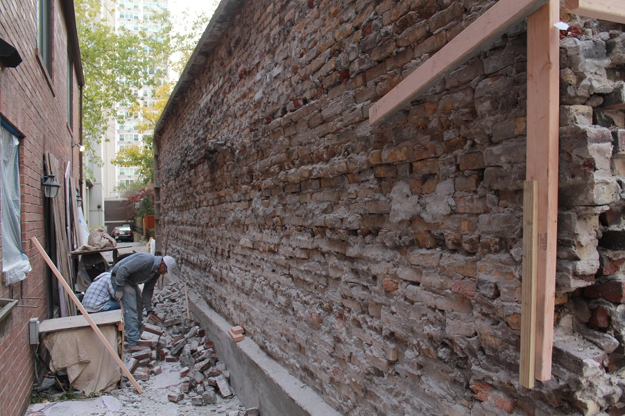 Man observing damaged brick wall