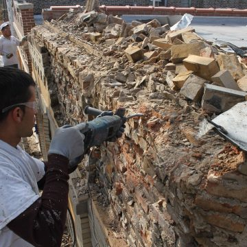 Man drilling into damaged brick