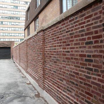 Brick wall leading to a garage door