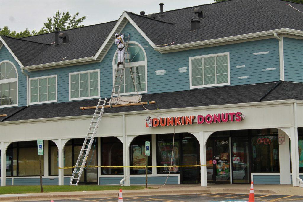 Man on ladder renovating building