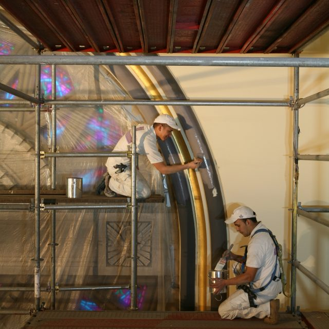 Two men painting in a church on scaffolding